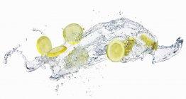 Tranches de citron dans les projections d'eau — Photo de stock