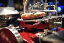 Вид крупным планом на кусок ветчины Пармы в режущей машине — стоковое фото
