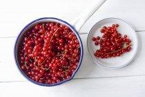 Grosellas rojas en cacerola y en plato - foto de stock