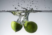 Limes falling into water — Stock Photo