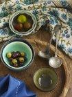 Plusieurs bols d'olives et de tomates sur la surface en bois avec serviette — Photo de stock