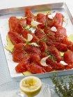 Помидоры на подносе для выпечки с тимьяном, чесноком и оливковым маслом на подносе — стоковое фото