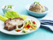 Pork chop served with salad — Stock Photo