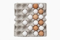 White and brown eggs in egg box — Stock Photo