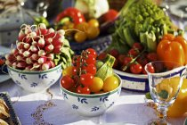 Fresh summer vegetables on a table in pots and bowls over table — Stock Photo