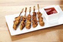 Kebabs de pollo con salsa de barbacoa en bandeja sobre superficies de madera - foto de stock