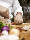 Closeup view of a chef slicing a chilli pepper on wooden desk — Stock Photo