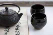 Чайник и чай черный чаши — стоковое фото