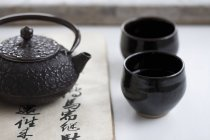 Teapot and black tea bowls — Stock Photo