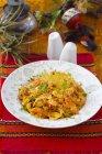 Un piatto di nasi goreng su una tovaglietta rossa sulla zolla bianca sopra un asciugamano rosso — Foto stock