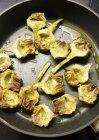 Fried artichoke hearts in a pan — Stock Photo