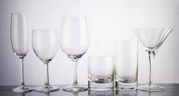 Vari bicchieri vuoti in una riga su fondo bianco — Foto stock