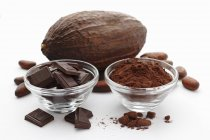 Cuadrados de chocolate y una vaina de cacao - foto de stock