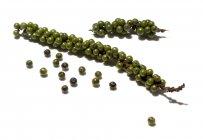 Vista de cerca de granos de pimienta verde fresca en la superficie blanca - foto de stock