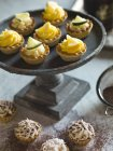Vista del primo piano di lime, limone e cocco crostate e vicino al piatto piedistallo — Foto stock