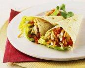 Pollo y verduras envolturas en plato blanco sobre toalla rojo - foto de stock