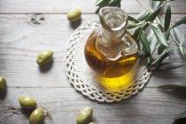 Vista de perto de óleo em uma garrafa com um ramo de azeitona e azeitonas — Fotografia de Stock
