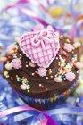 Шоколадний кекс увінчаний рожеве серце — стокове фото