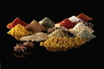 Closeup view of various spices heaps on black reflective surface — Stock Photo