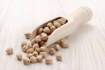 Pois chiches dans une cuillère en bois sur une surface en bois — Photo de stock