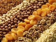 Vista de primer plano de los frutos secos surtidos y frutos secos en filas - foto de stock