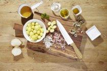 Ингредиенты для приготовления Теплый картофельный салат с ромашками на деревянные поверхности с стол и нож — стоковое фото