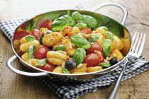 Gnocchi with tomatoes, olives, pine nuts and basil in wok over towel — Stock Photo