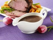Closeup view of creamy gravy with meat and vegetable dish by flowers — Stock Photo