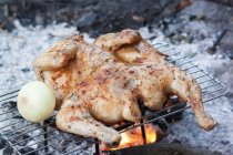 Chicken cooking on barbecue rack — Stock Photo
