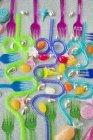 Visão geral gráfica de plástico colorido festa garfos com palhas bebendo curvas azuis e roxos em fundo de purpurina prata com doces — Fotografia de Stock