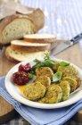 Frittelle di zucchine con basilico e pane sulla zolla bianca sopra tavolo — Foto stock