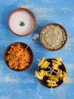 Вид зверху курячі тандури шампури з квіноа, морква салатом і раітой в чаші — стокове фото