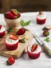 Cupcakes con crema y fresas - foto de stock