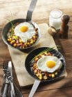 Fried potatoes and egg in frying pans — Stock Photo