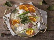 Окорочка с луком, апельсины и травы в сковороде на деревянные поверхности — стоковое фото