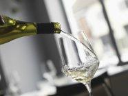 Наливая вино белое в стекло — стоковое фото