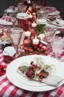 Christmas table laid with a red checkered tablecloth, candles, napkins and jars of jam — Stock Photo