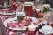 Vista del primo piano della tavola di Natale posato con una tovaglia a quadretti rossa, tovaglioli, vasetti di marmellata e candele — Foto stock