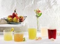 Крупный план различных лимонадов с яблоками и розой — стоковое фото
