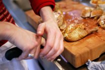 Closeup view of person cutting roasted chicken with a knife — Stock Photo