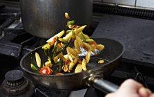 Légumes sont sautées dans une casserole sur une plaque de cuisson — Photo de stock