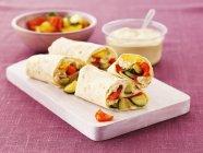 Impacchi con hummus, cetriolo e peperoni su una tavola sopra superficie rosa — Foto stock