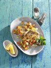 Crispy zander on root vegetables in white plate over blue surface — Stock Photo
