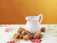 Fudge and jug of cream — Stock Photo