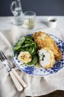 Chicken Kiev with spinach on white and blue plate over cloth — Stock Photo