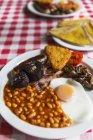 Colazione all'inglese su piatto bianco sopra la tovaglia — Foto stock