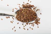 Spoonful of organic flax seeds — Stock Photo