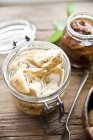 Preserved artichoke hearts and dried tomatoes in jars over wooden surface — Stock Photo