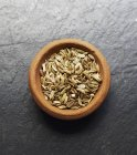 A bowl of fennel seeds over wooden surface — Stock Photo