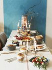 Laid table with different dishes and burning candles — Stock Photo